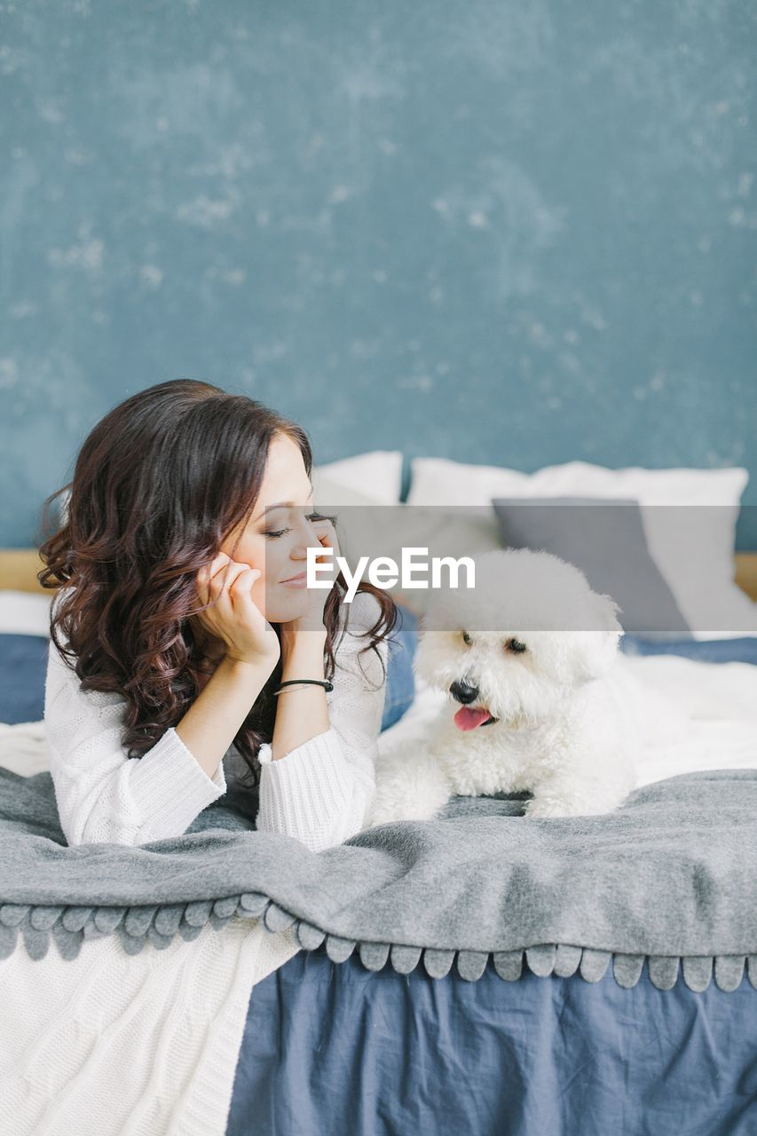 Young woman looking at poodle puppy while lying on bed at home