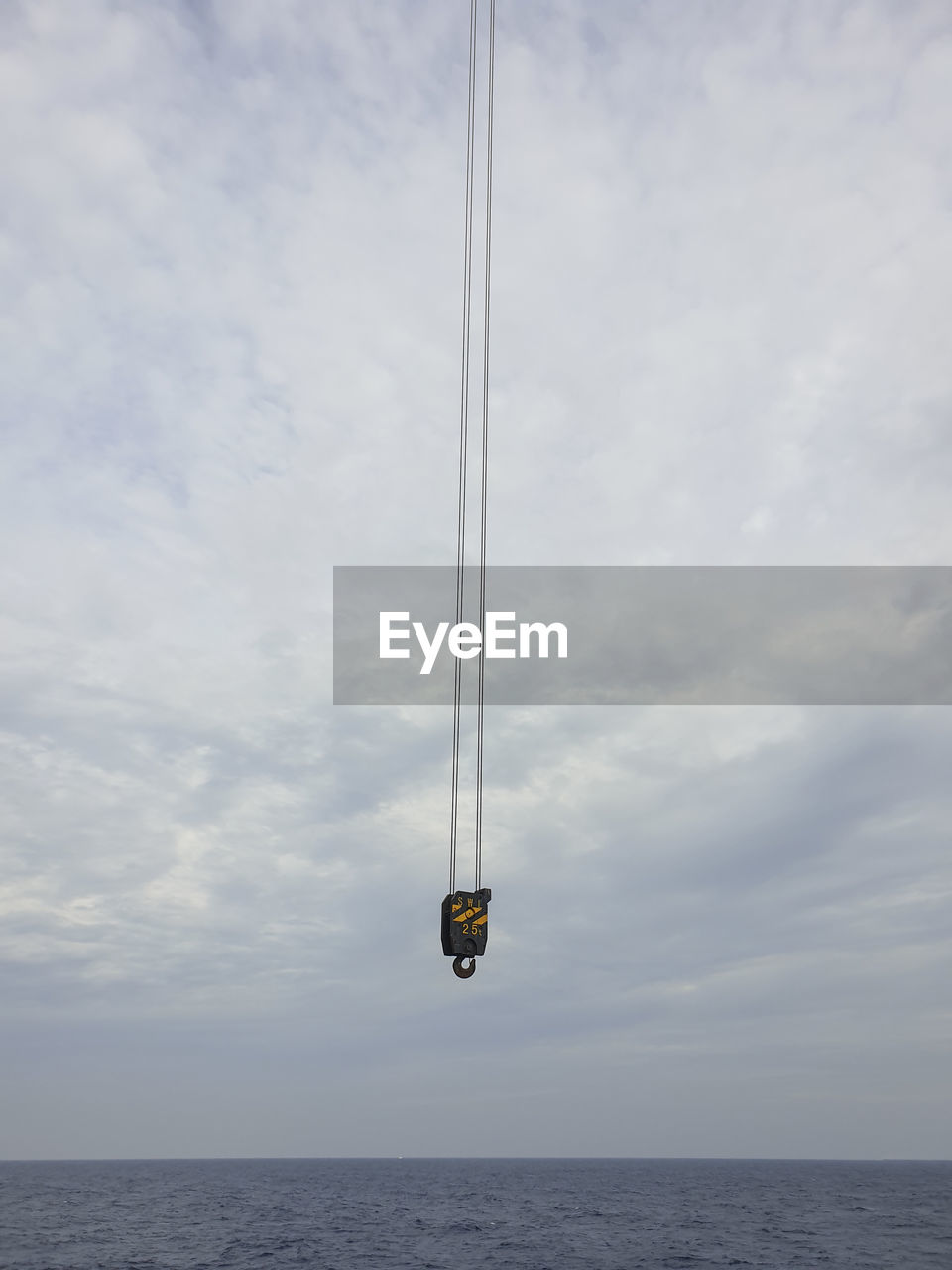 LOW ANGLE VIEW OF HELICOPTER IN SEA AGAINST SKY