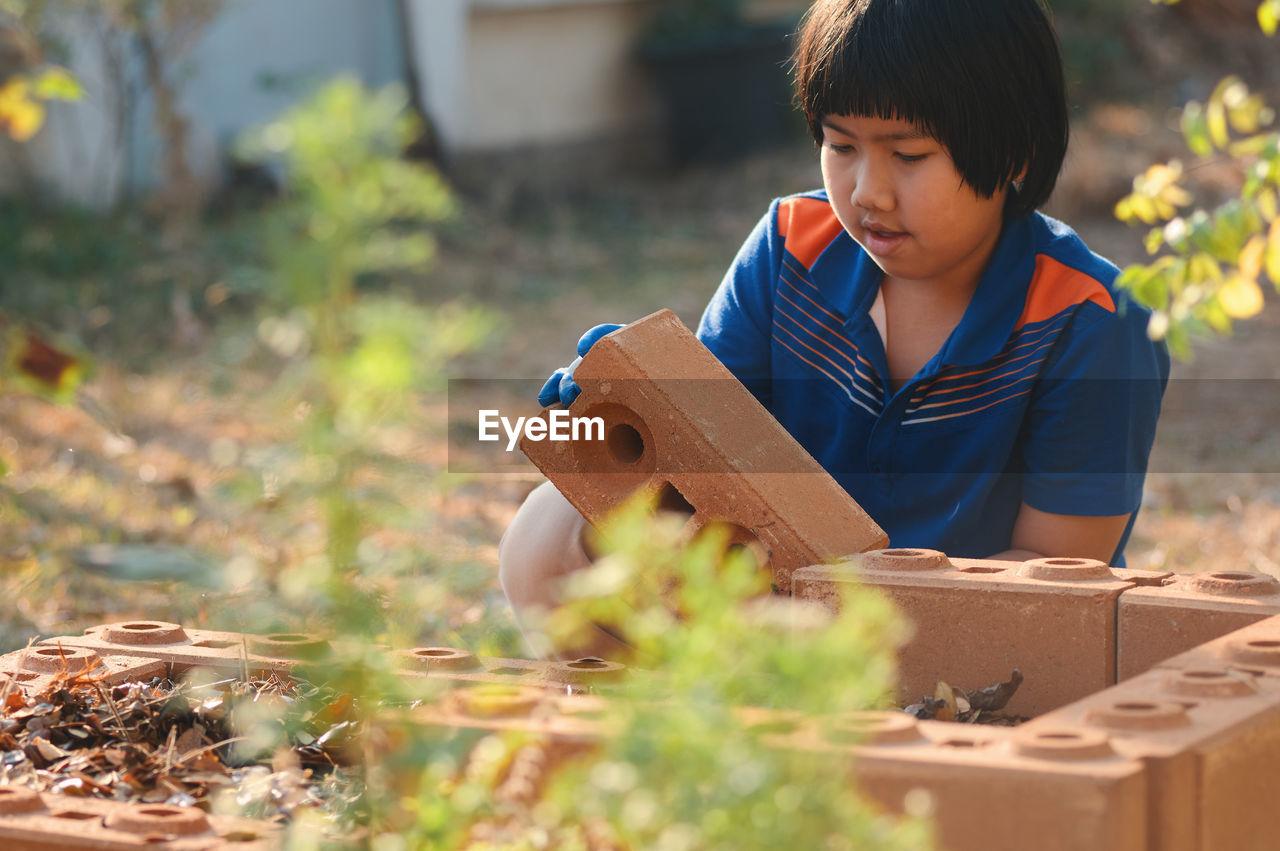 Boy arranging bricks outdoors