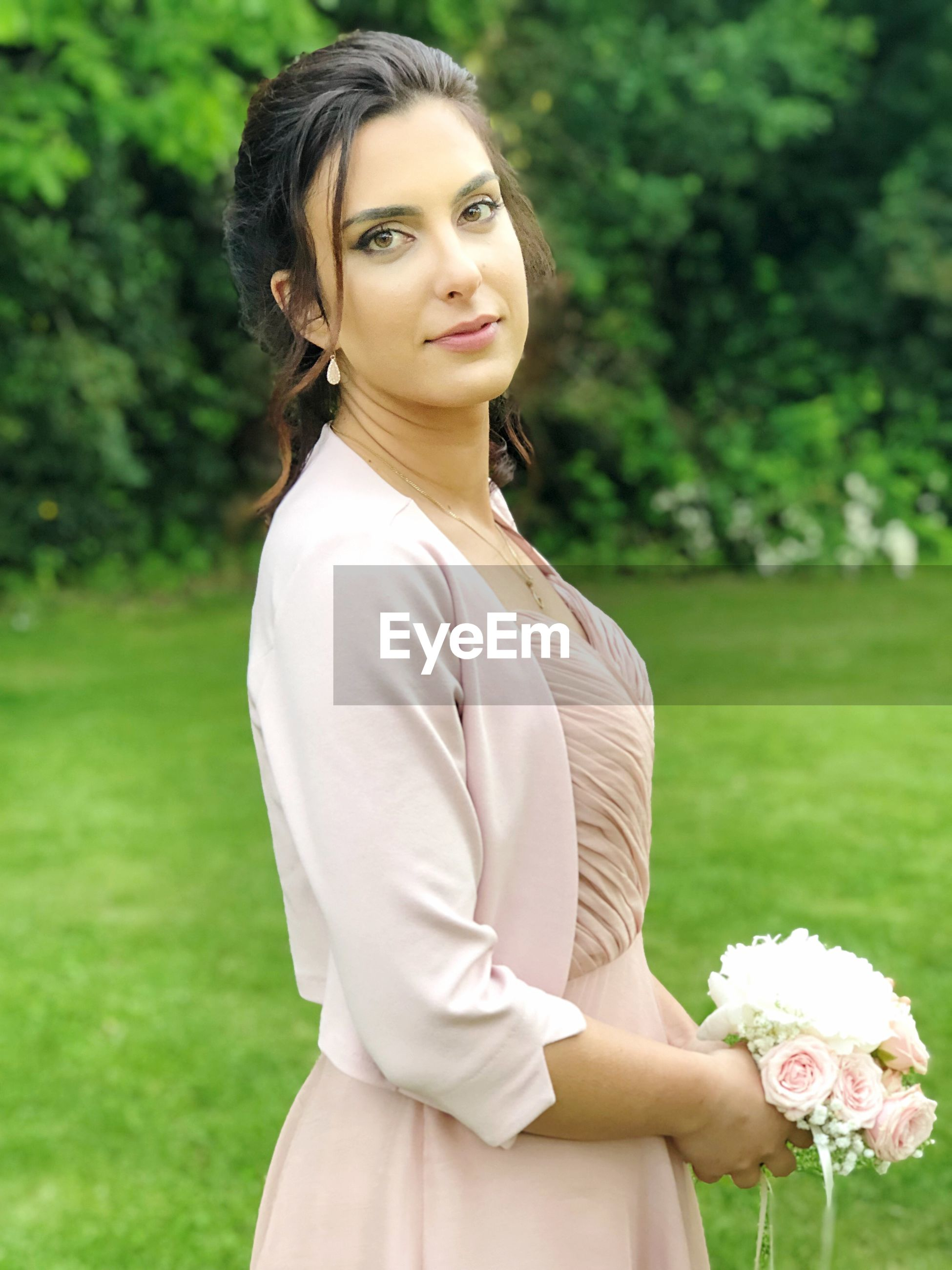 Portrait of beautiful woman with bouquet standing on land