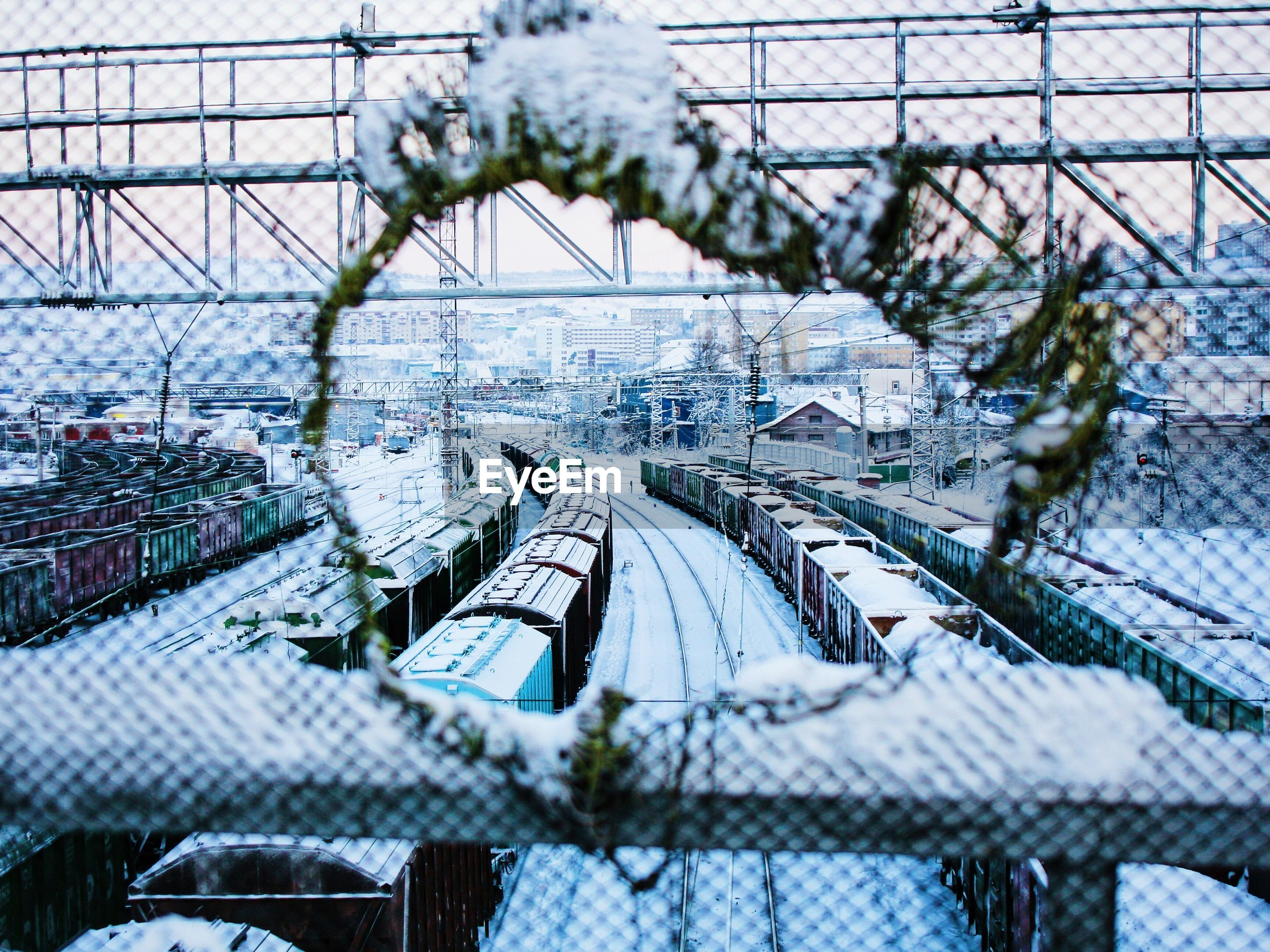 Trains on snow covered field seen through hole in fence