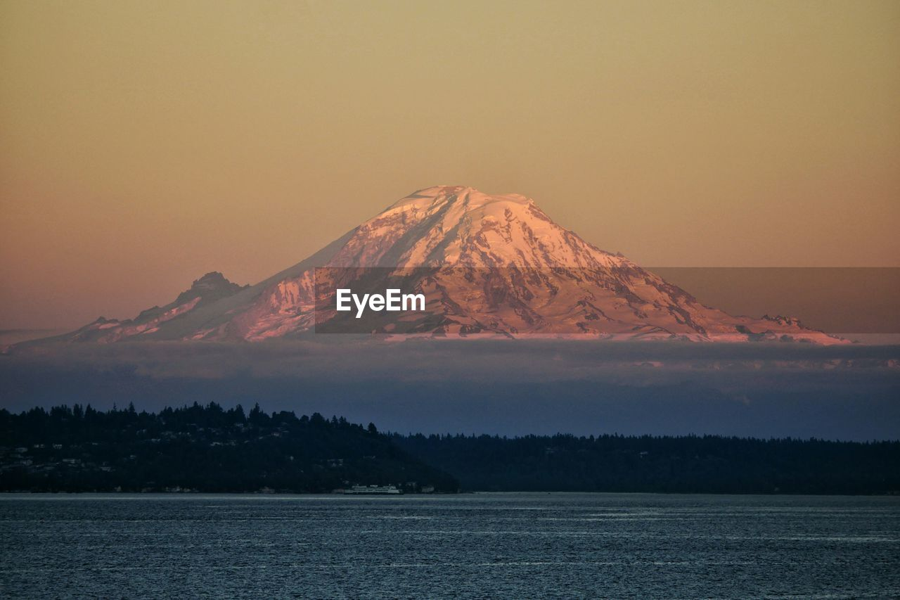 View of calm lake against mountain peak