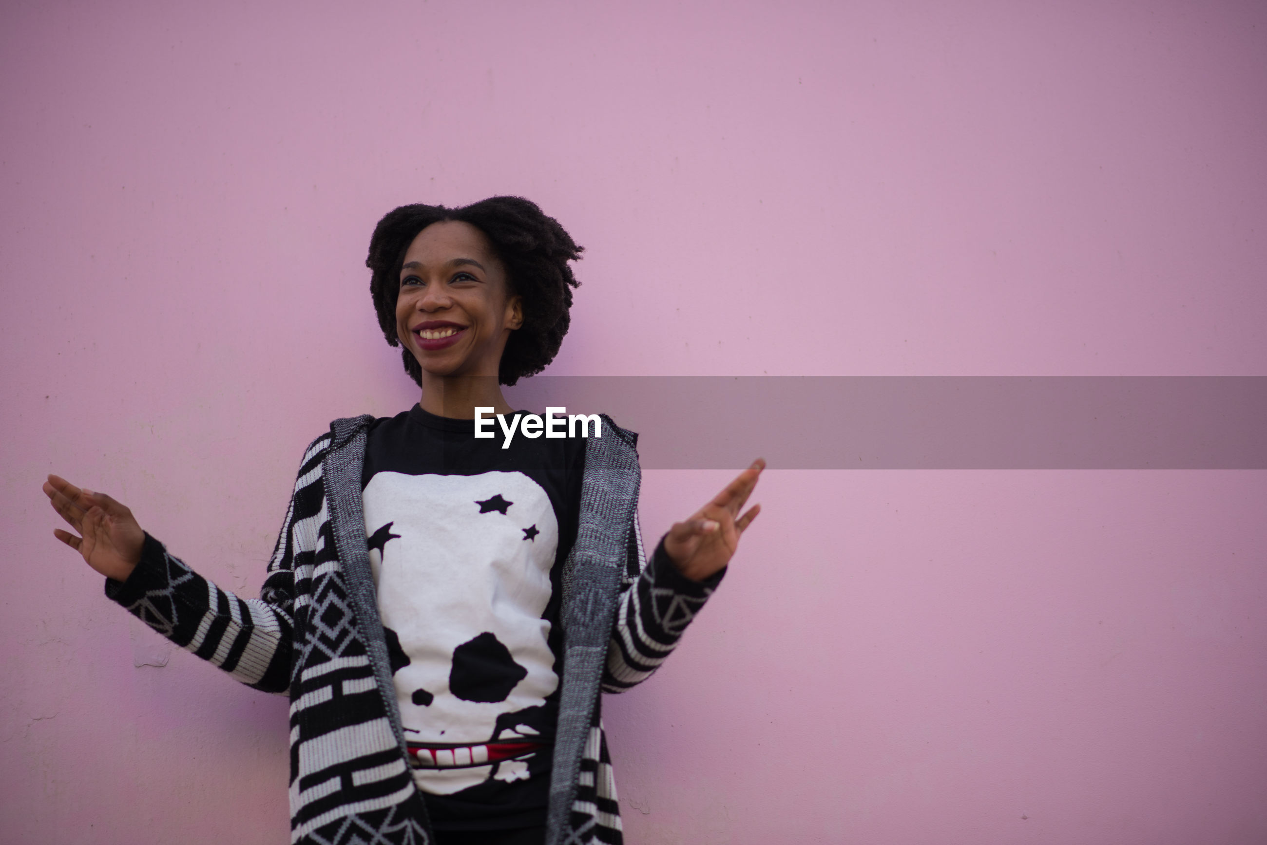 Low angle view of woman smiling while standing pink wall