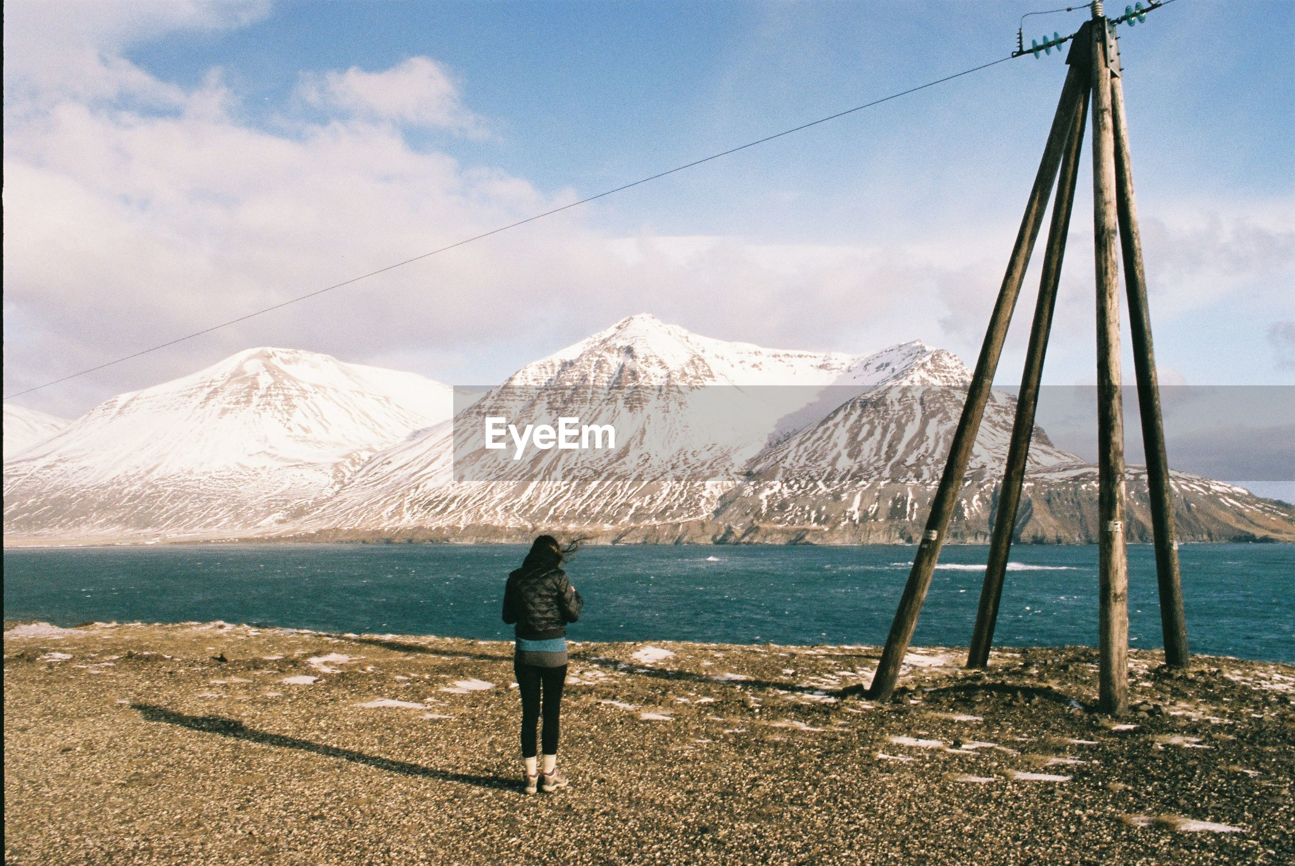 mountain, one person, cloud - sky, water, rear view, beauty in nature, scenics - nature, sky, real people, nature, day, leisure activity, standing, full length, lifestyles, mountain range, non-urban scene, land, snowcapped mountain, outdoors