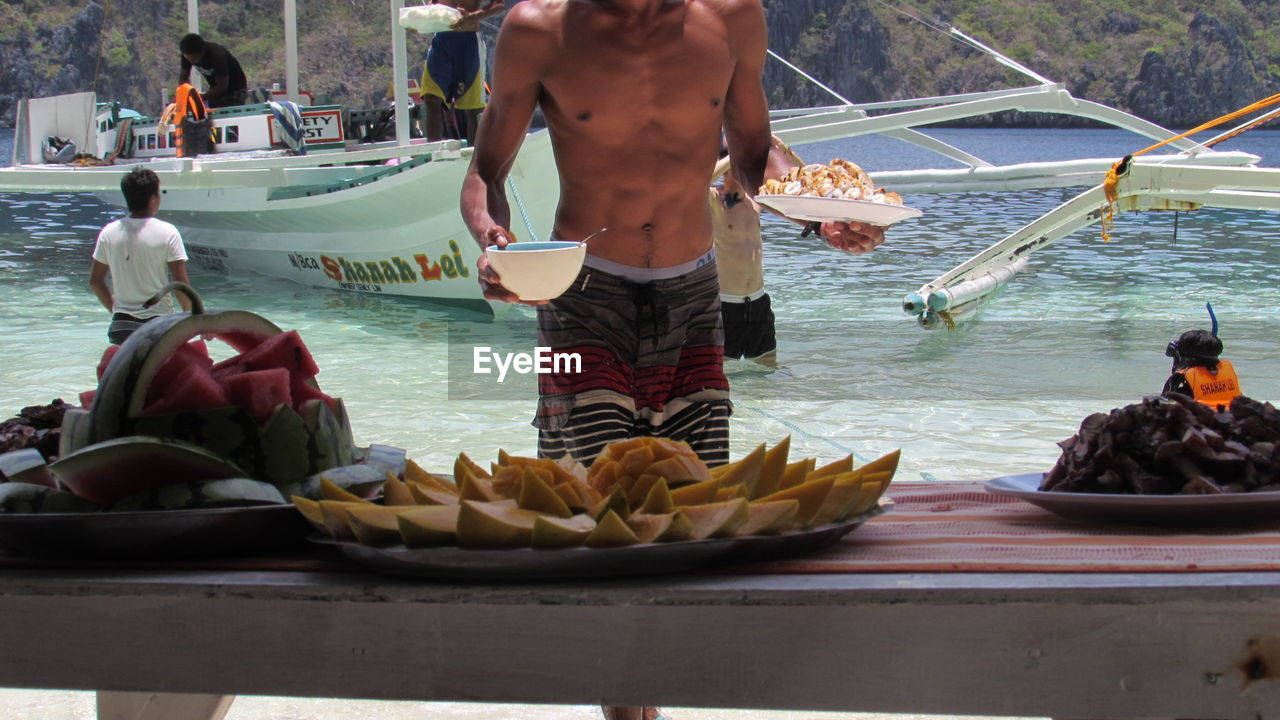 real people, leisure activity, men, water, lifestyles, day, nautical vessel, food and drink, outdoors, women, food, standing, one person