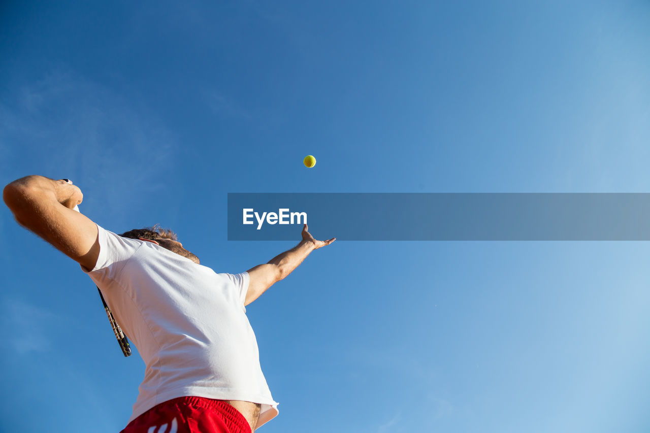 Low angle view of man playing with ball against blue sky