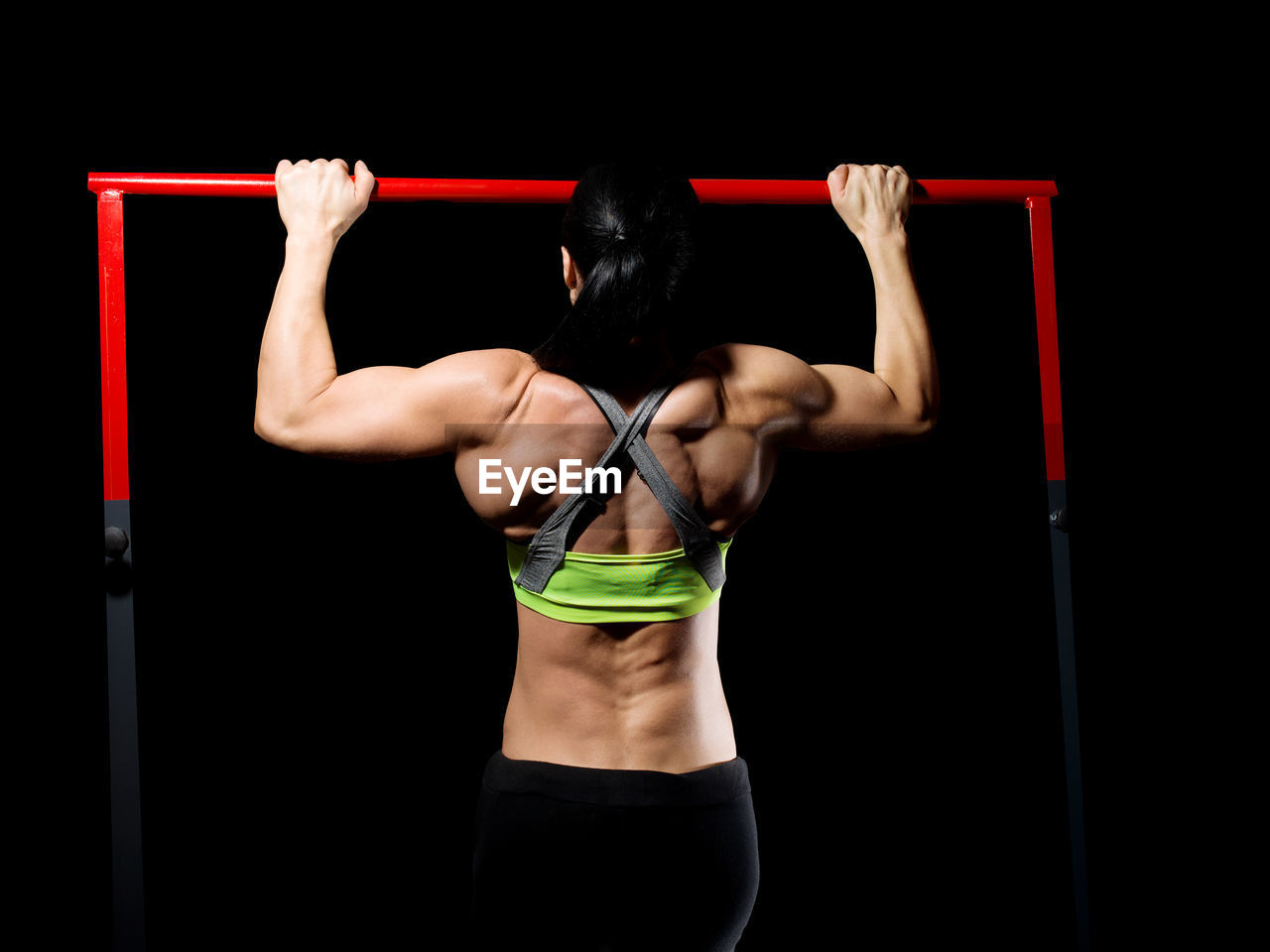 Woman exercising against black background