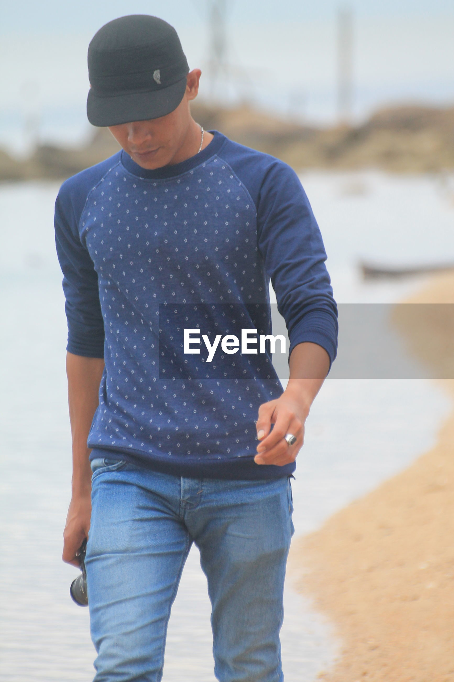 one person, real people, casual clothing, land, beach, standing, three quarter length, focus on foreground, leisure activity, day, lifestyles, water, front view, men, fashion, sunglasses, glasses, sand, outdoors