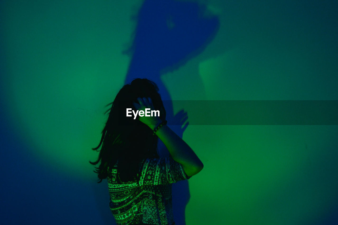Woman standing against illuminated green wall with shadow