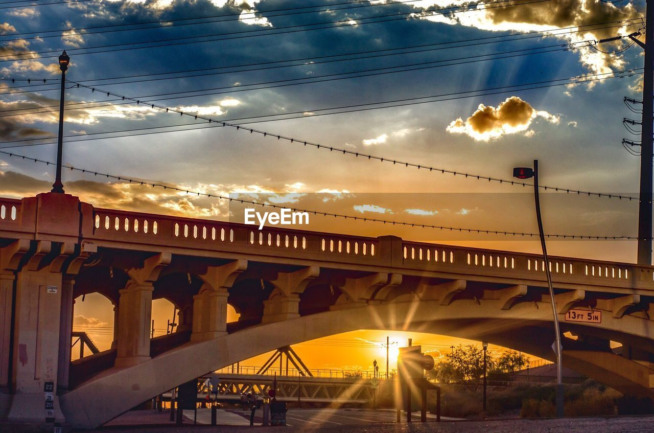 transportation, sky, bridge - man made structure, connection, architecture, sunset, cloud - sky, built structure, low angle view, train - vehicle, sun, rail transportation, cable, outdoors, mode of transport, illuminated, sunlight, travel, public transportation, nature, no people, city, day