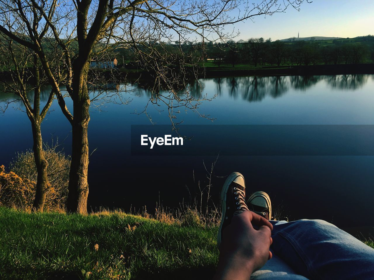water, lake, plant, tree, reflection, real people, nature, body part, one person, human body part, low section, beauty in nature, personal perspective, leisure activity, grass, tranquil scene, tranquility, lifestyles, shoe, outdoors, finger, human foot