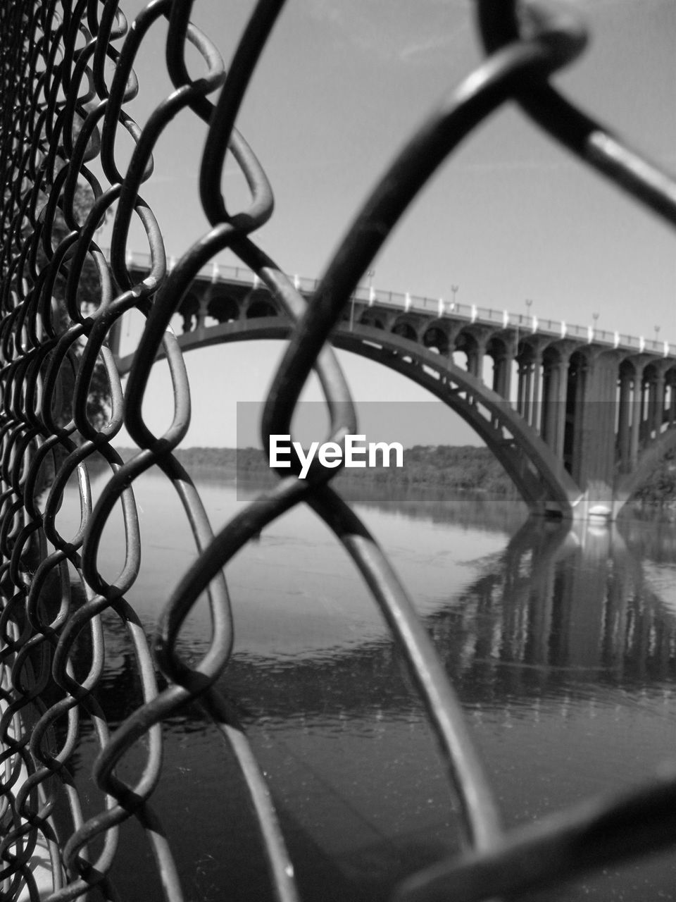 Bridge over river seen through chainlink fence