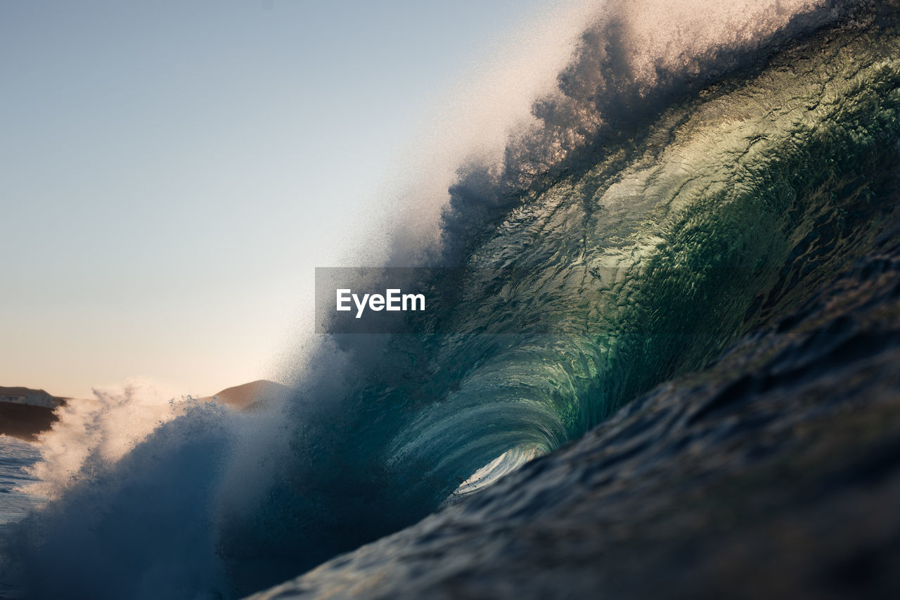 A powerful wave breaking under the sunset