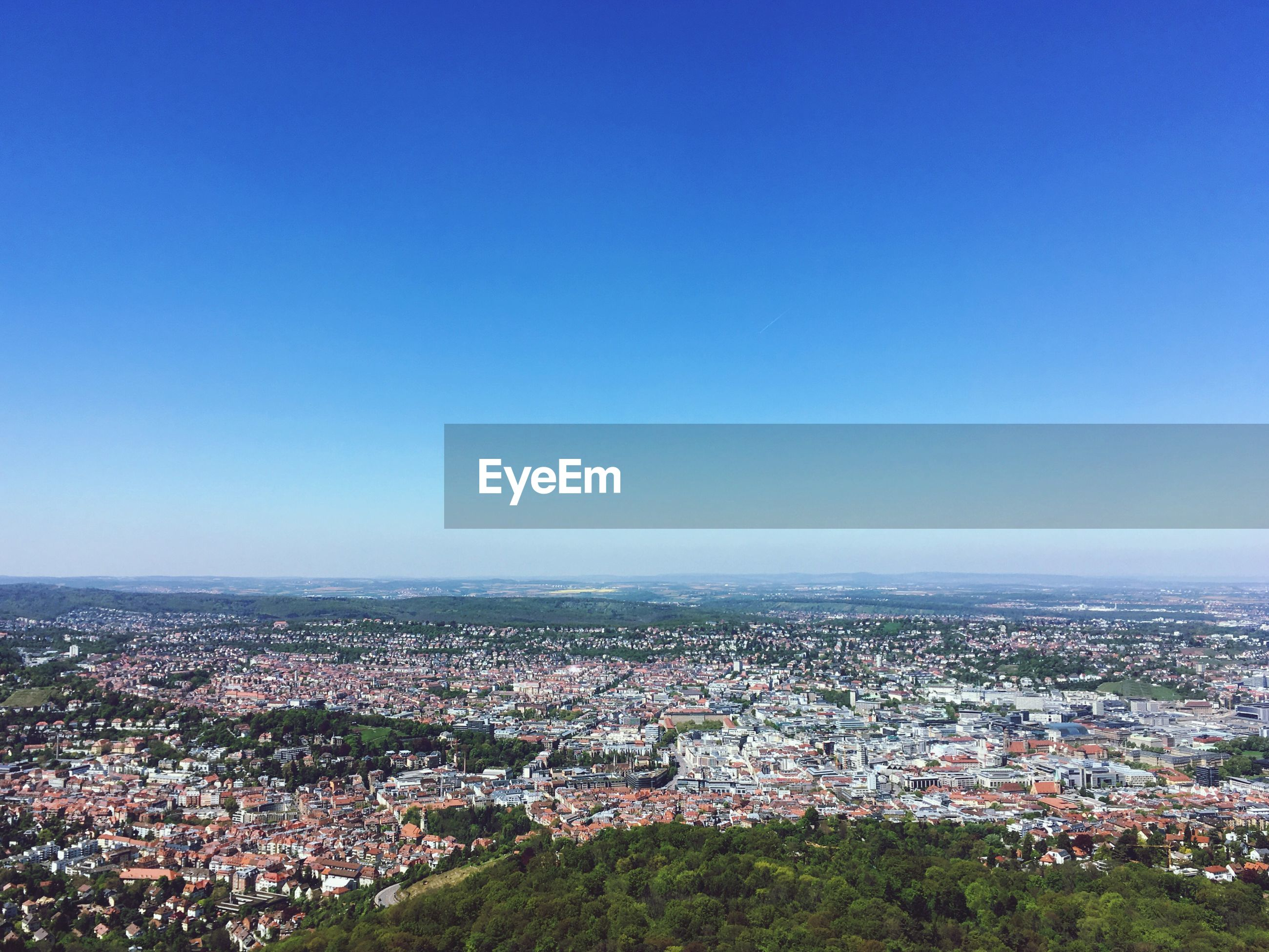 HIGH ANGLE VIEW OF TOWN AGAINST CLEAR BLUE SKY