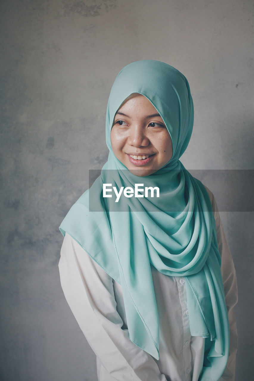 Smiling Young Woman Wearing Hijab While Standing Against Wall