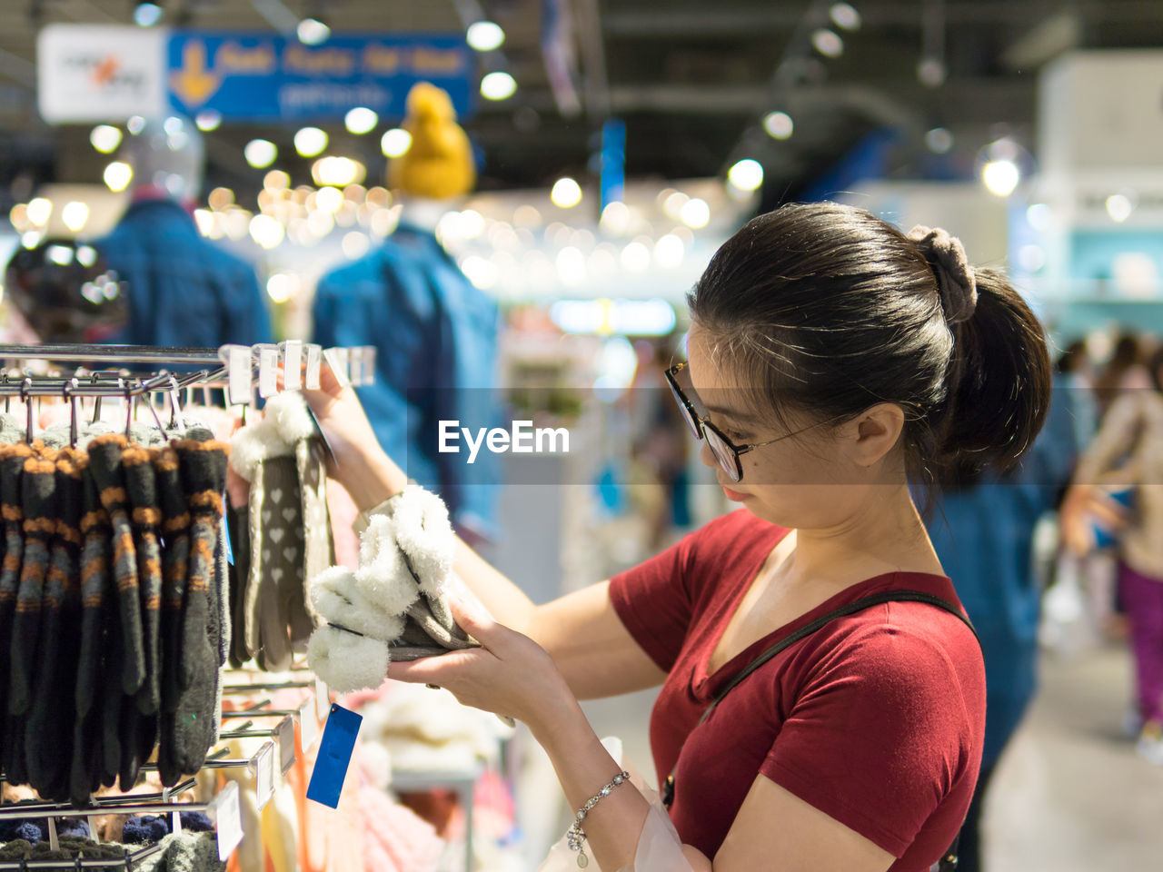 one person, real people, retail, women, focus on foreground, market, looking, casual clothing, indoors, adult, standing, business, choice, lifestyles, shopping, store, customer, leisure activity, retail display, hairstyle, sale, buying, consumerism