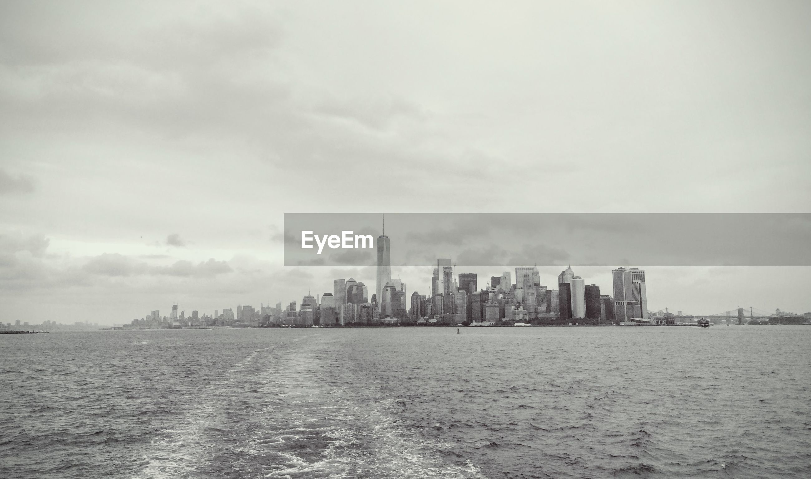 Scenic view of sea by city against cloudy sky