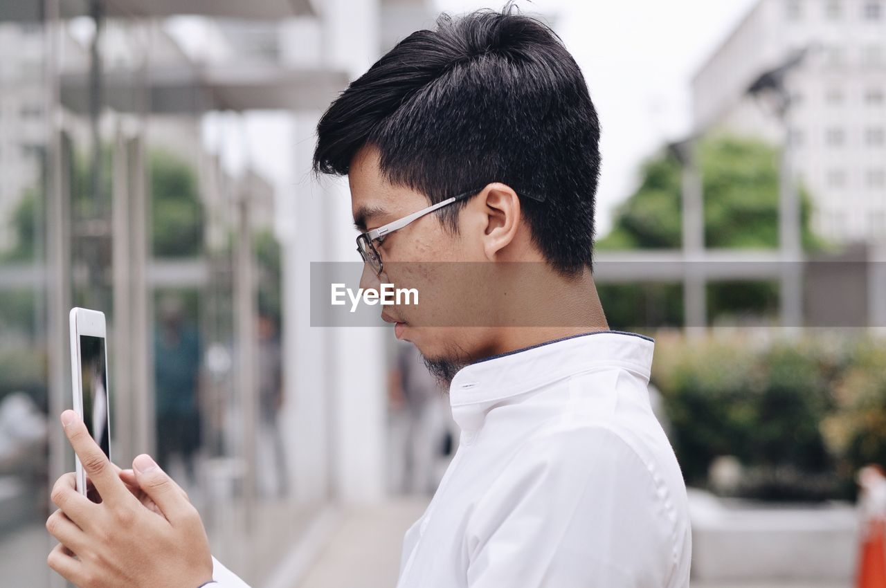 Side view of young man wearing eyeglasses using smart phone in city