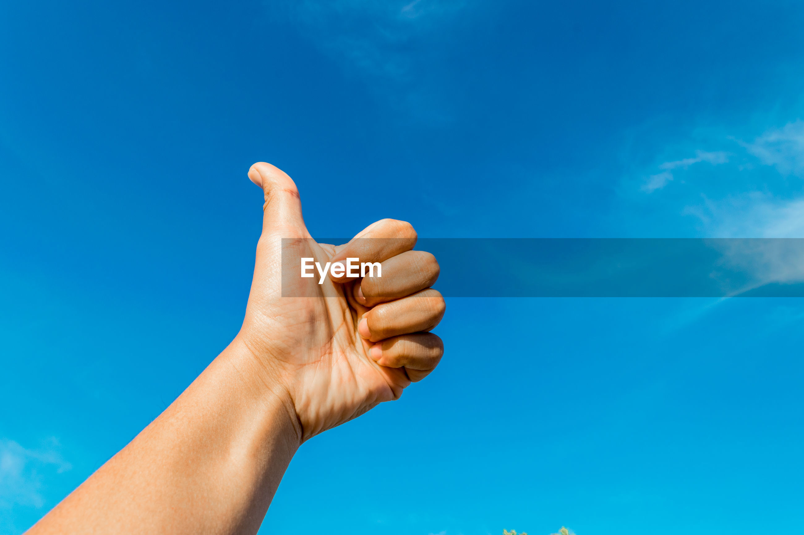 Cropped hand gesturing thumbs up against blue sky