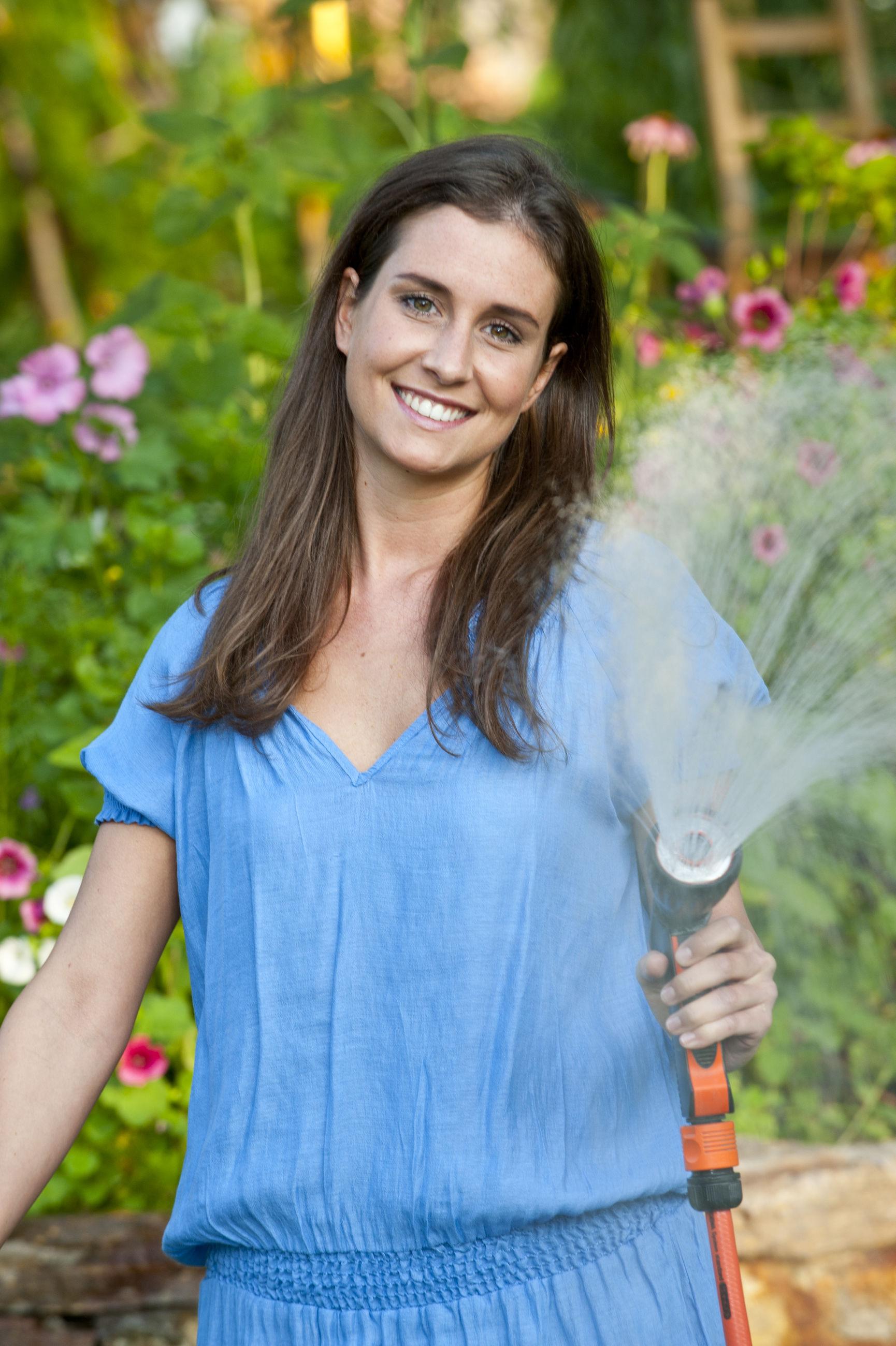 Portrait of woman watering plants