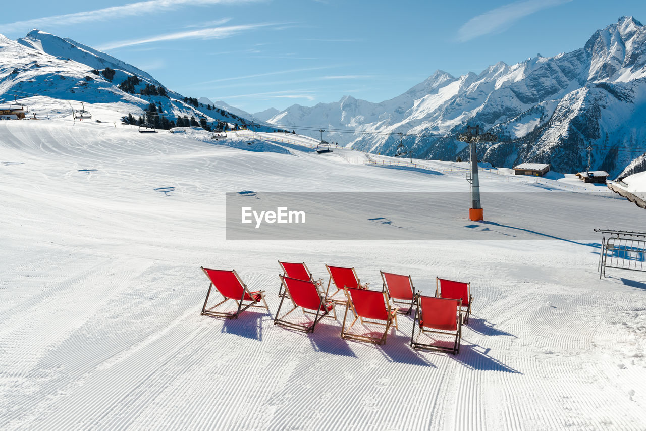 Deck Chairs On Snow Covered Mountain Against Sky