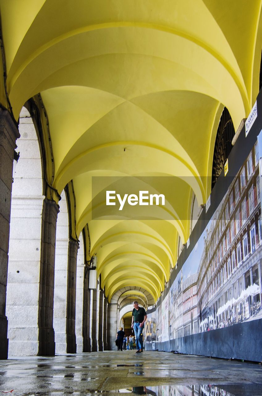 architecture, built structure, arch, real people, yellow, direction, indoors, the way forward, day, lifestyles, building, adult, people, two people, walking, men, ceiling, incidental people, women, architectural column