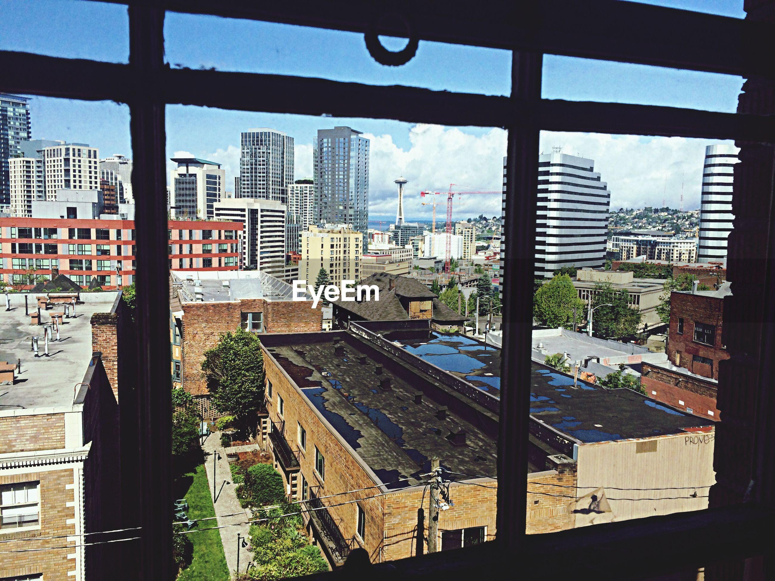 View of buildings against sky through window