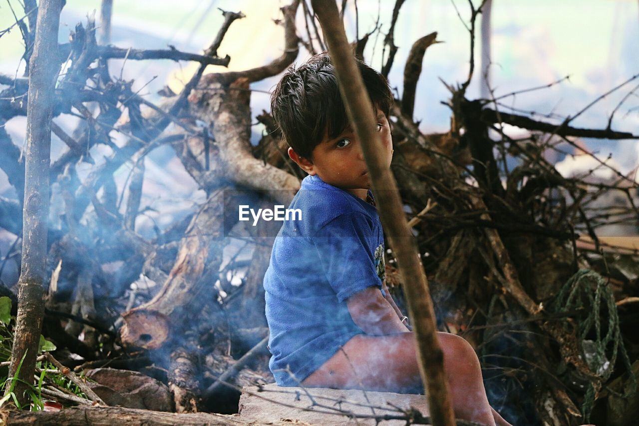 Young Indian Boy Sitting By Bonfire