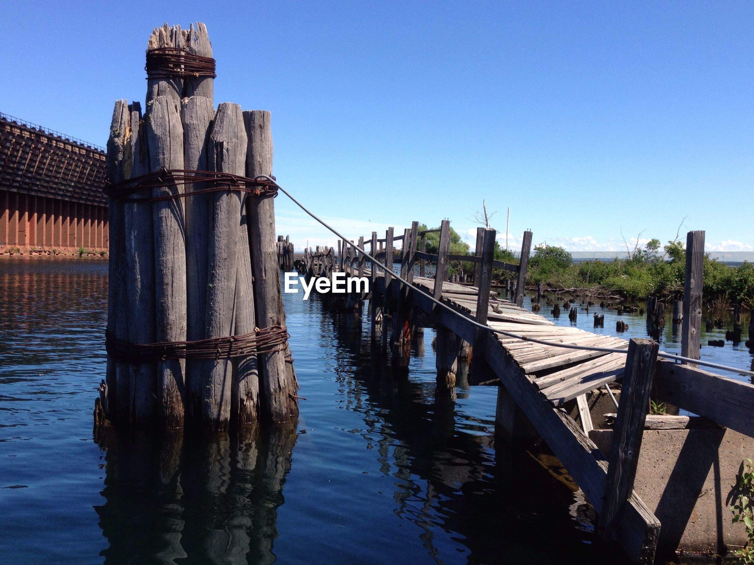 Old pier over lake against blue sky