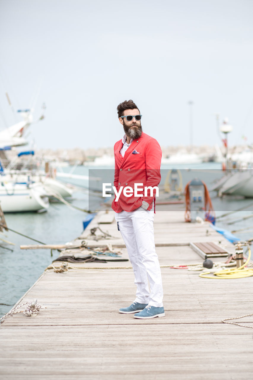 Mature Handsome Bearded Man With Hands In Pockets Standing On Pier