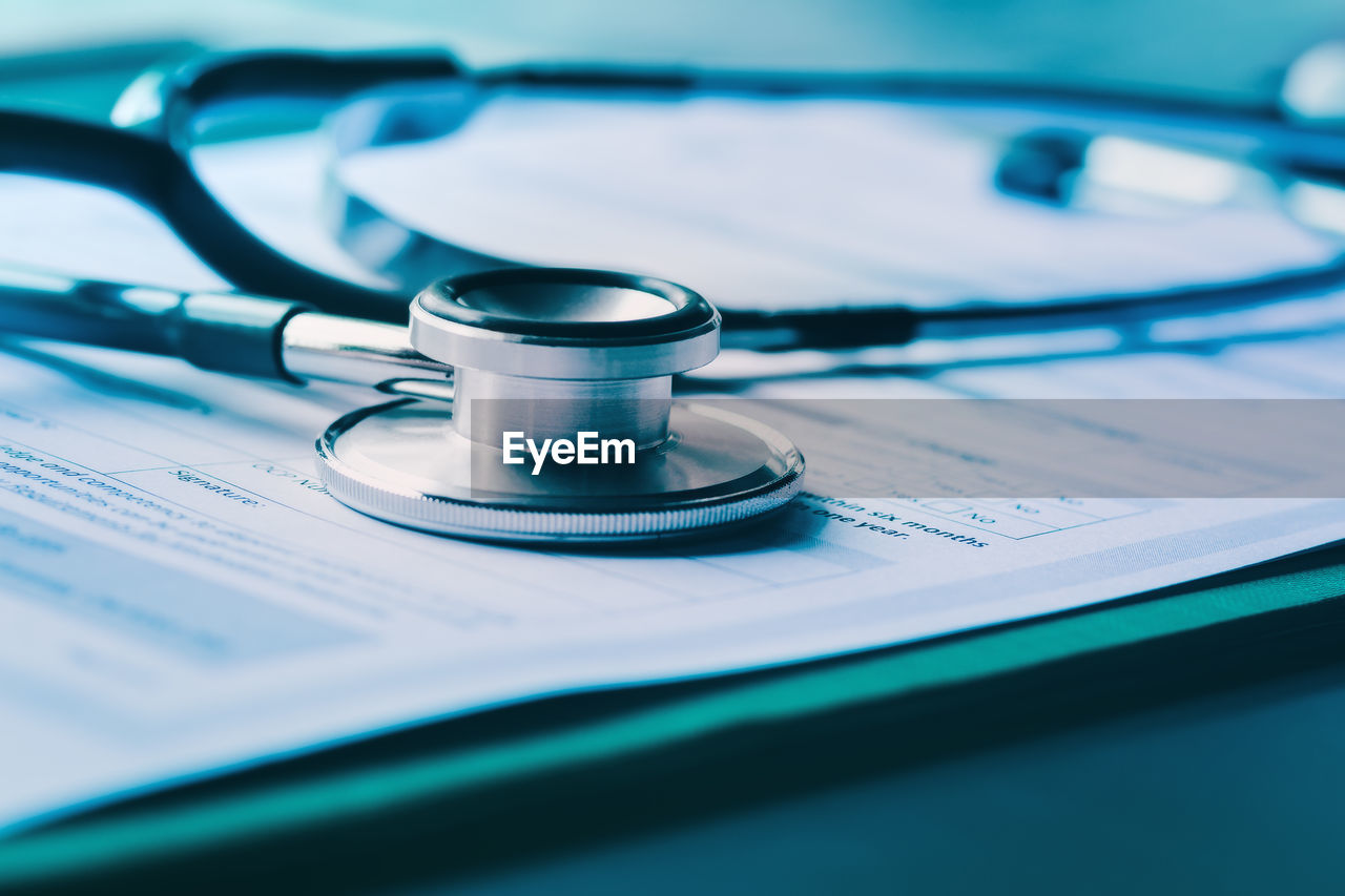 stethoscope, medical instrument, medical supplies, medical equipment, healthcare and medicine, selective focus, close-up, indoors, still life, paper, no people, table, publication, accuracy, blue, text, education, arts culture and entertainment, document, pulse trace