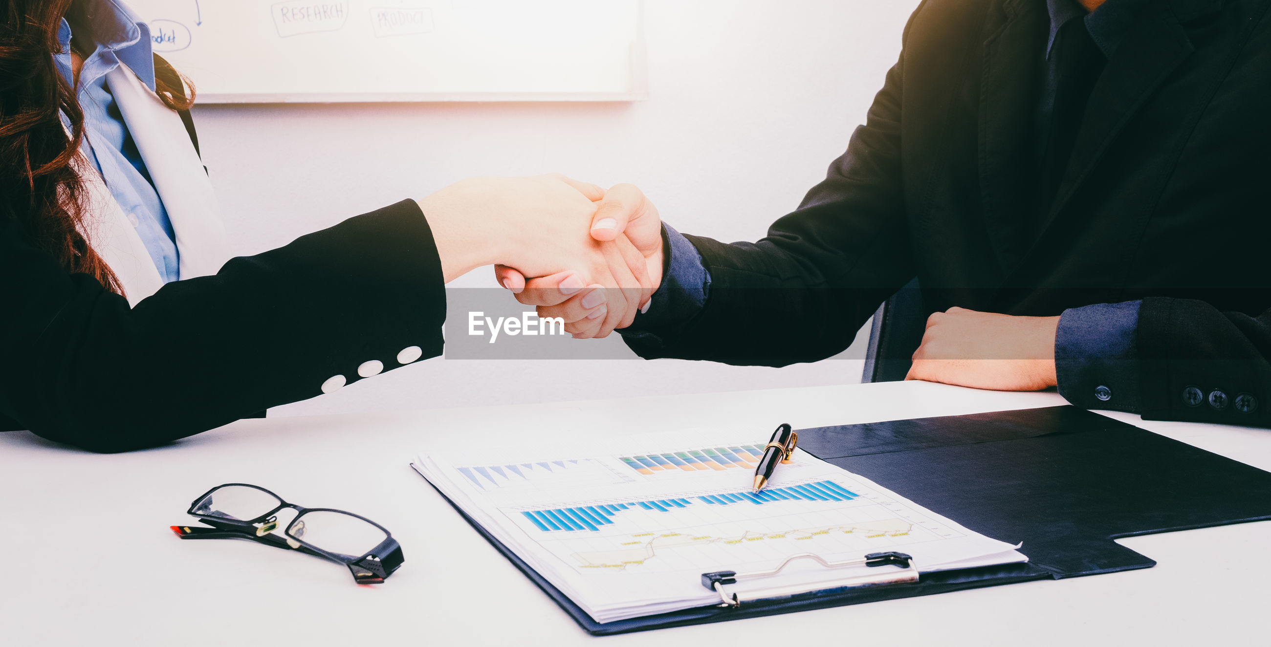 Midsection of business colleagues shaking hands while sitting at desk in office