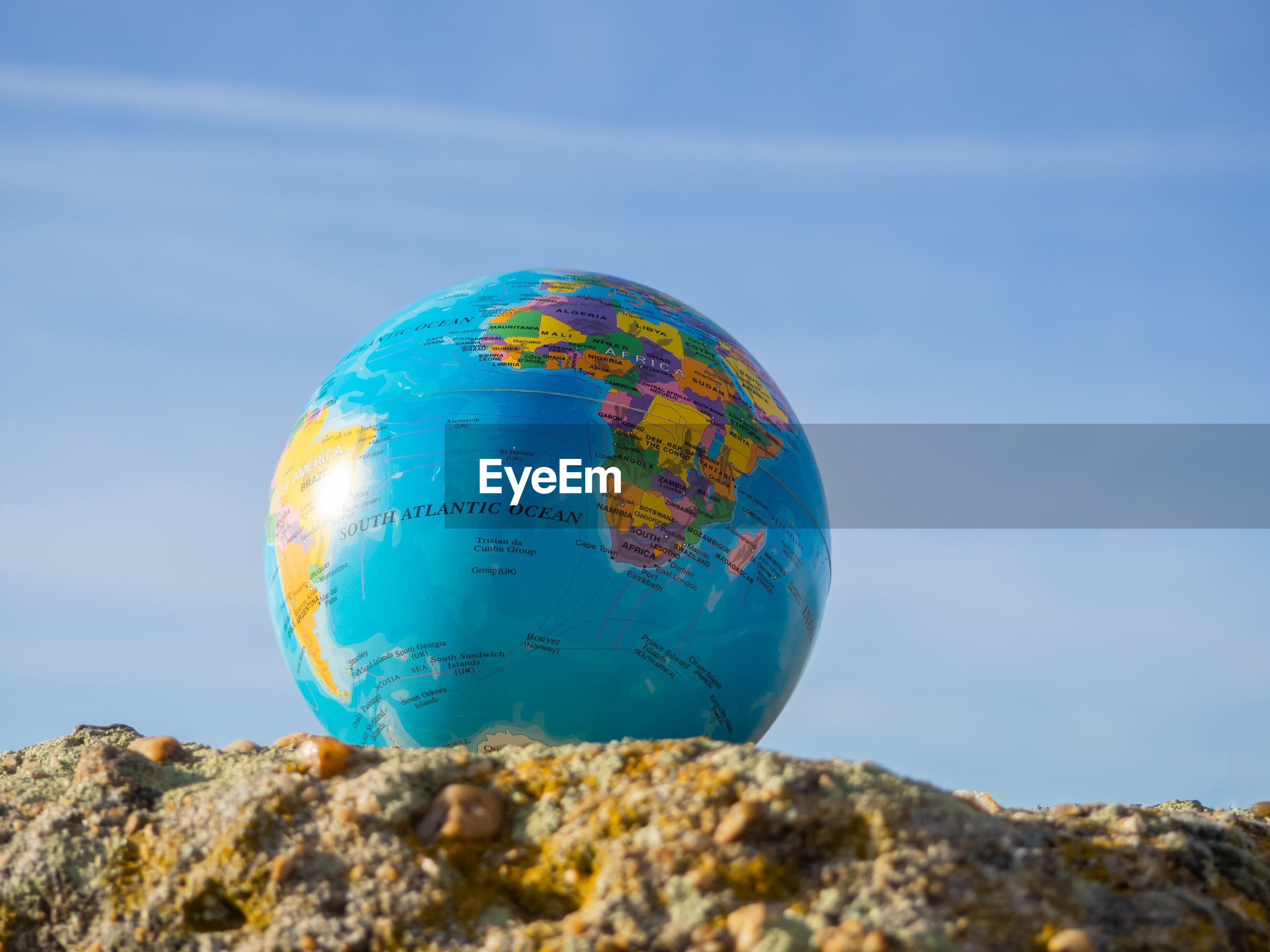 Low angle view of globe on rock against blue sky