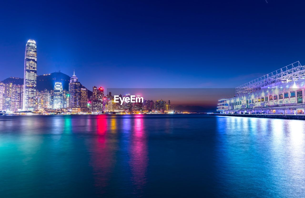 building exterior, architecture, built structure, illuminated, city, building, night, waterfront, office building exterior, water, sky, skyscraper, reflection, urban skyline, cityscape, blue, no people, landscape, nature, tall - high, modern, outdoors, financial district, luxury, nightlife
