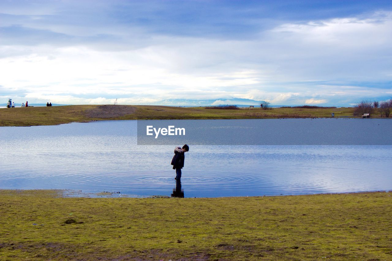 Boy Standing Amidst Lake At Park Against Cloudy Sky