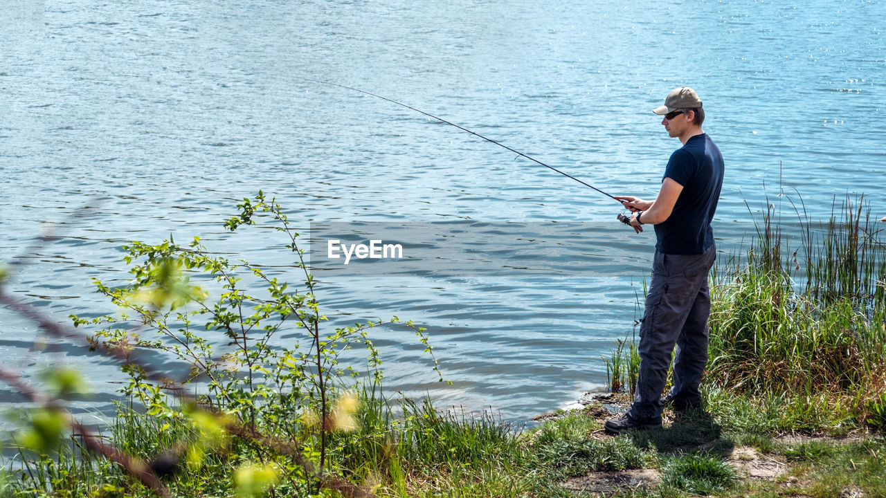 Fisherman with spinning rod on nature background. angler man with fishing spinning