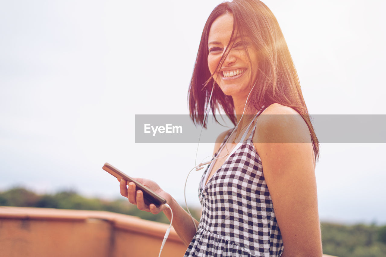 technology, communication, wireless technology, one person, lifestyles, connection, young adult, smiling, leisure activity, sky, real people, young women, happiness, mobile phone, holding, portable information device, standing, emotion, looking, focus on foreground, hairstyle, hair, outdoors, beautiful woman