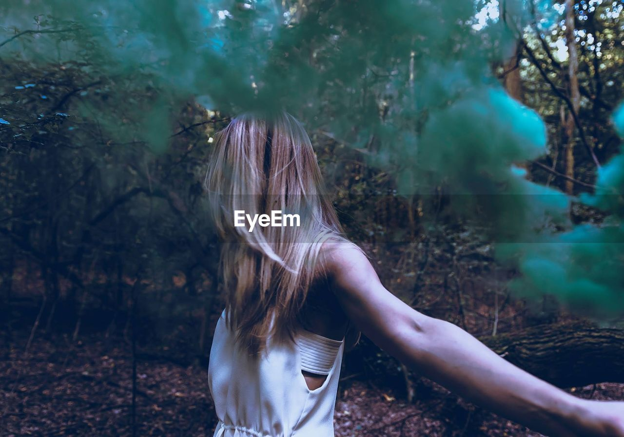 Young Woman Standing By Green Smoke In Forest