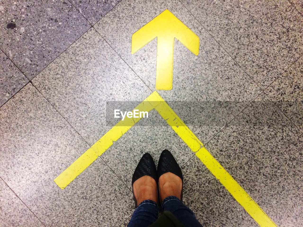 Low Section Of Woman Wearing Shoes Standing By Arrow Sign On Tiled Floor