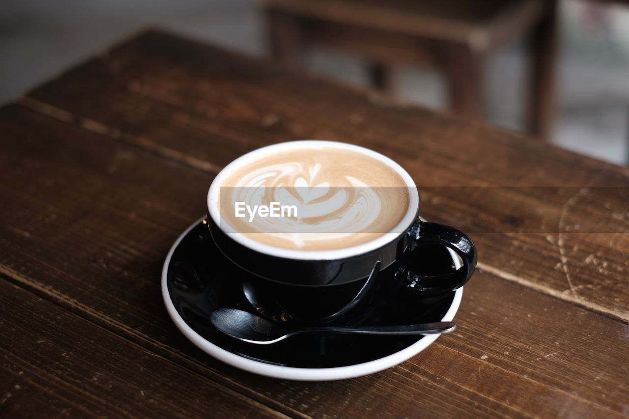 coffee - drink, coffee, drink, refreshment, coffee cup, food and drink, cup, frothy drink, mug, table, cappuccino, crockery, saucer, froth art, still life, wood - material, hot drink, indoors, freshness, latte, no people, non-alcoholic beverage, froth