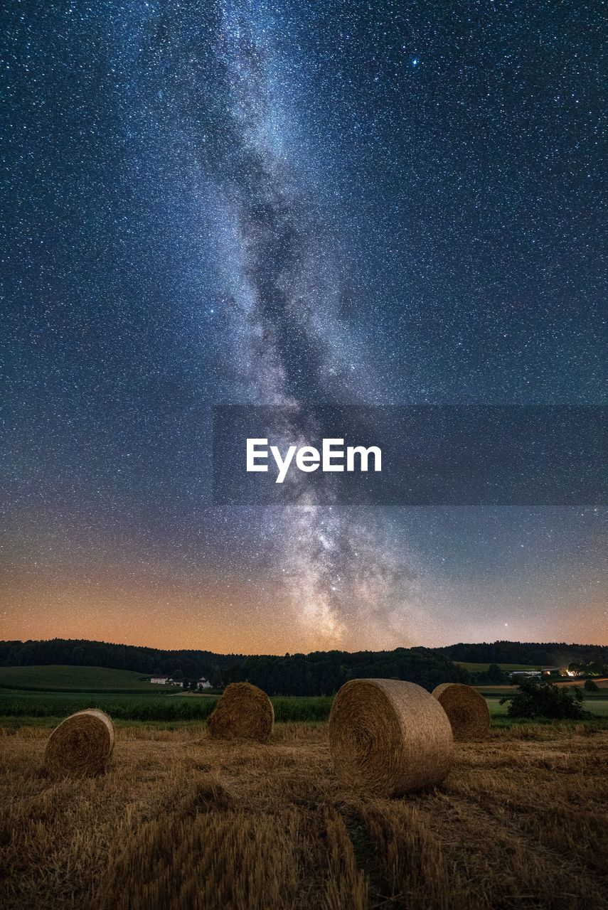 Scenic view of grassy field against star field at night