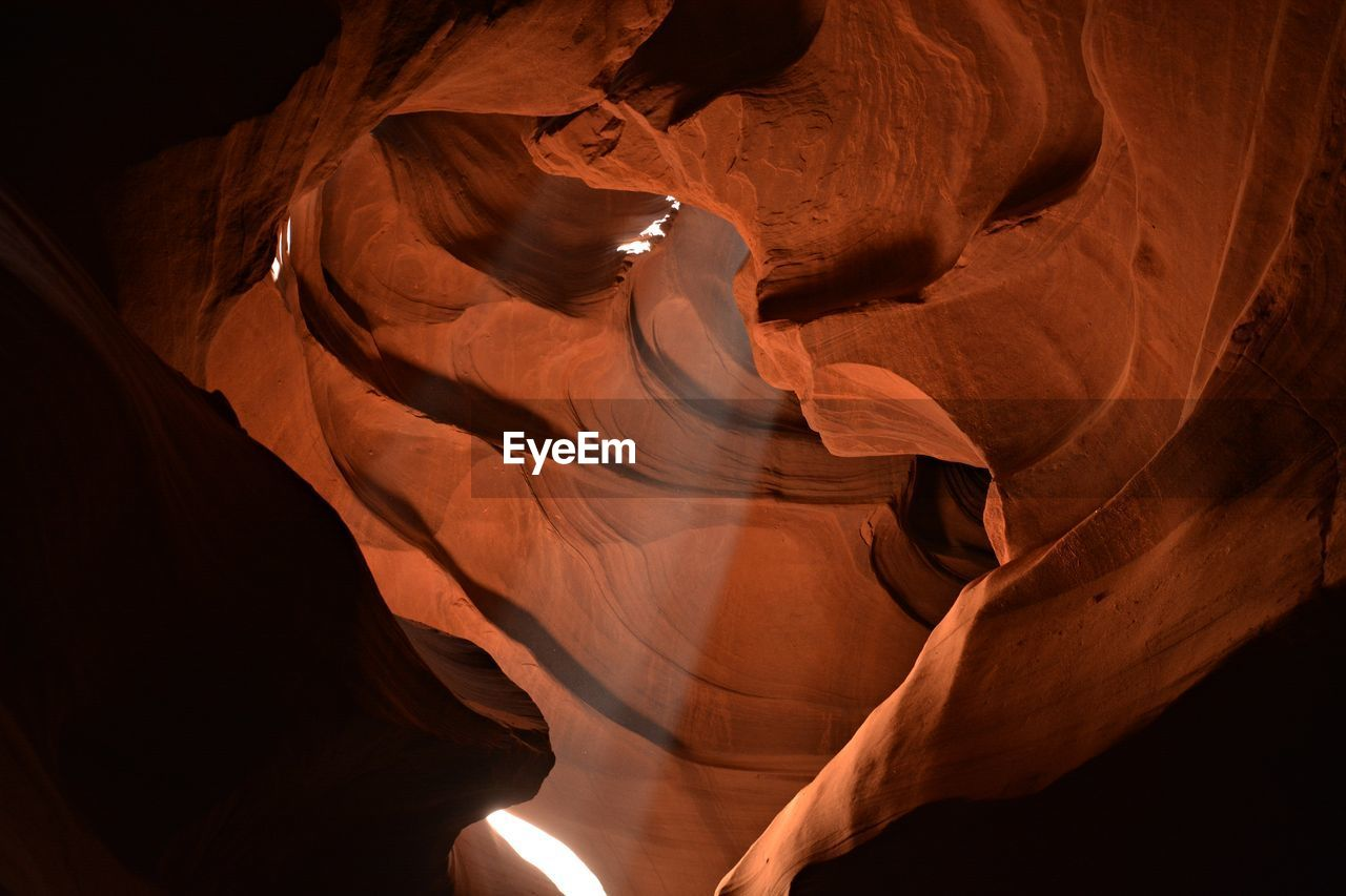 Low angle view of sunbeam streaming from rock formation in antelope canyon