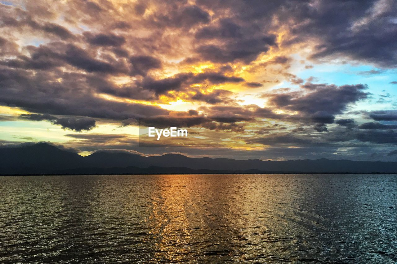 cloud - sky, sky, beauty in nature, scenics - nature, water, tranquil scene, sunset, tranquility, sea, idyllic, nature, waterfront, sunlight, no people, dramatic sky, non-urban scene, reflection, mountain, awe, outdoors
