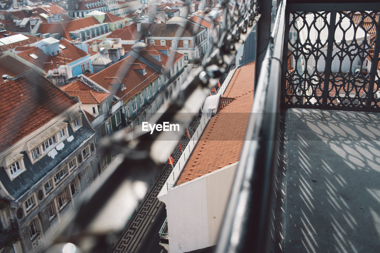 architecture, building exterior, built structure, city, high angle view, building, roof, residential district, day, selective focus, no people, transportation, nature, outdoors, mode of transportation, focus on background, metal, travel destinations, railing, cityscape, roof tile