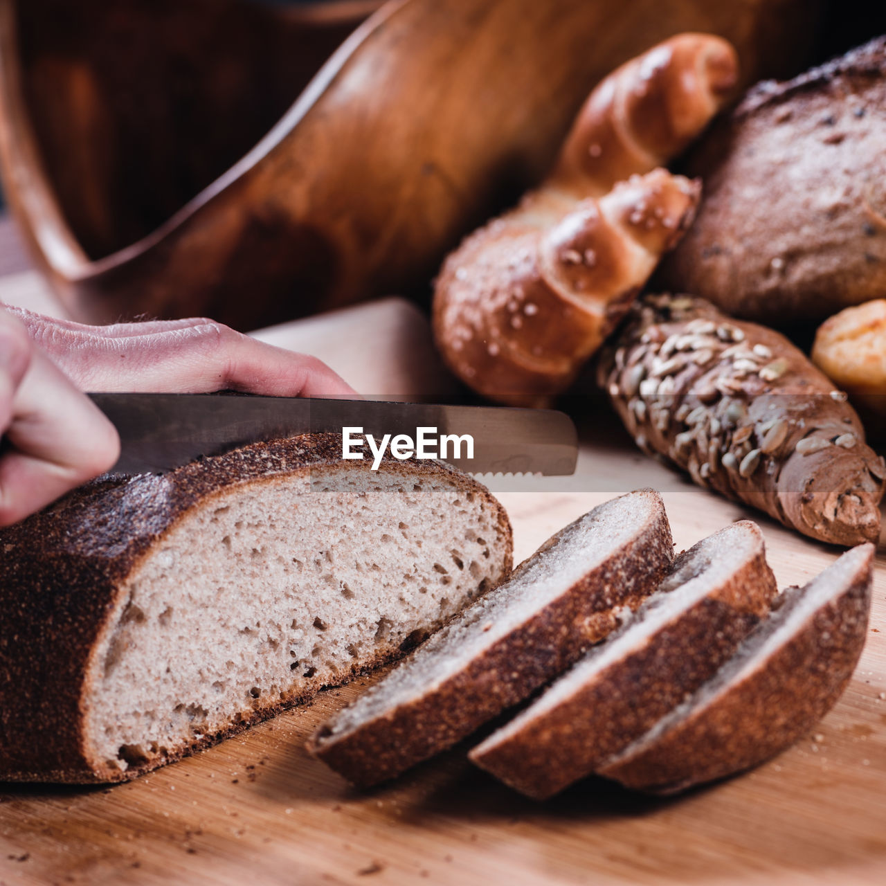 Cropped hand cutting bread on table