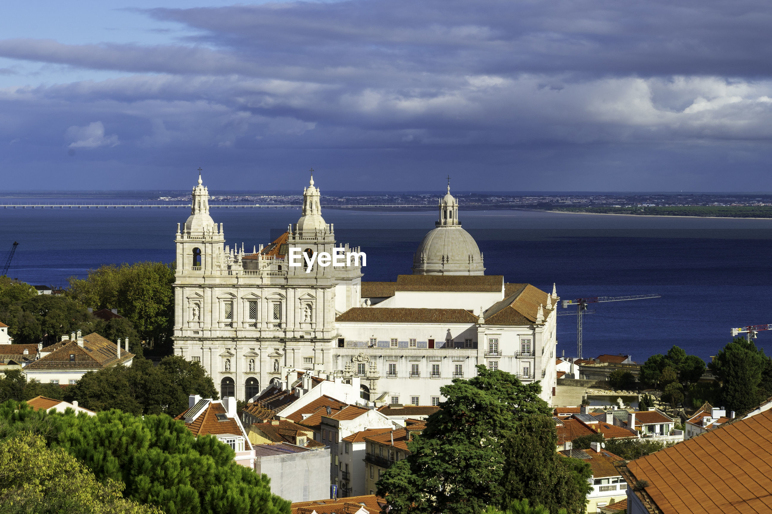 High angle view of two churches in front of the tejo river against cloudy sky
