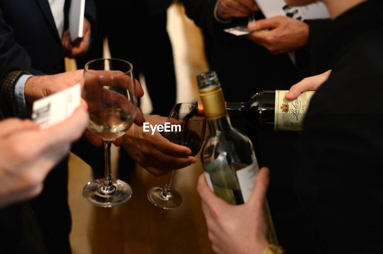 alcohol, drink, refreshment, food and drink, holding, human hand, group of people, real people, glass, hand, wine, human body part, indoors, men, midsection, friendship, adult, business, leisure activity, lifestyles, red wine