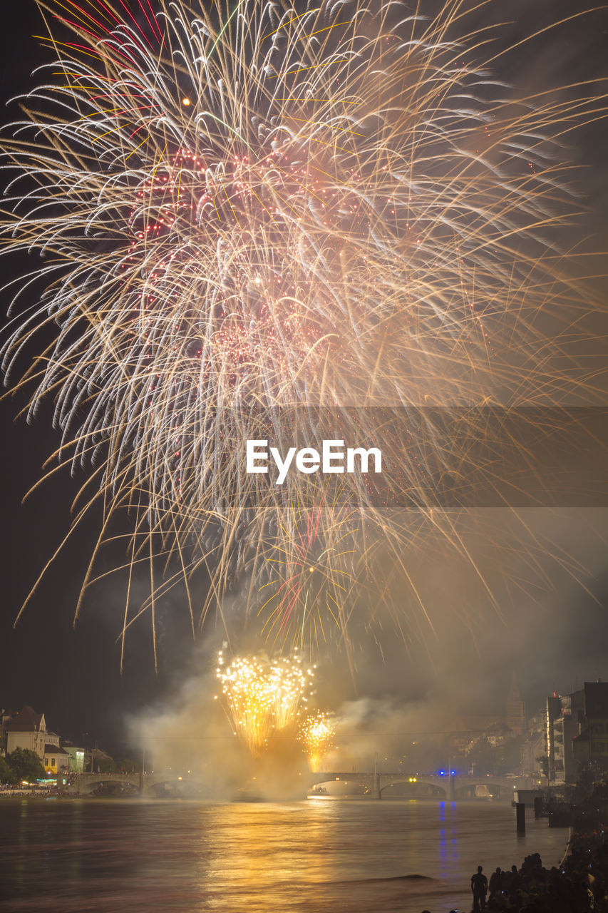 night, long exposure, firework display, illuminated, motion, exploding, firework - man made object, celebration, sparks, blurred motion, arts culture and entertainment, water, sky, no people, low angle view, firework, outdoors, waterfront, event, multi colored, architecture, building exterior, city