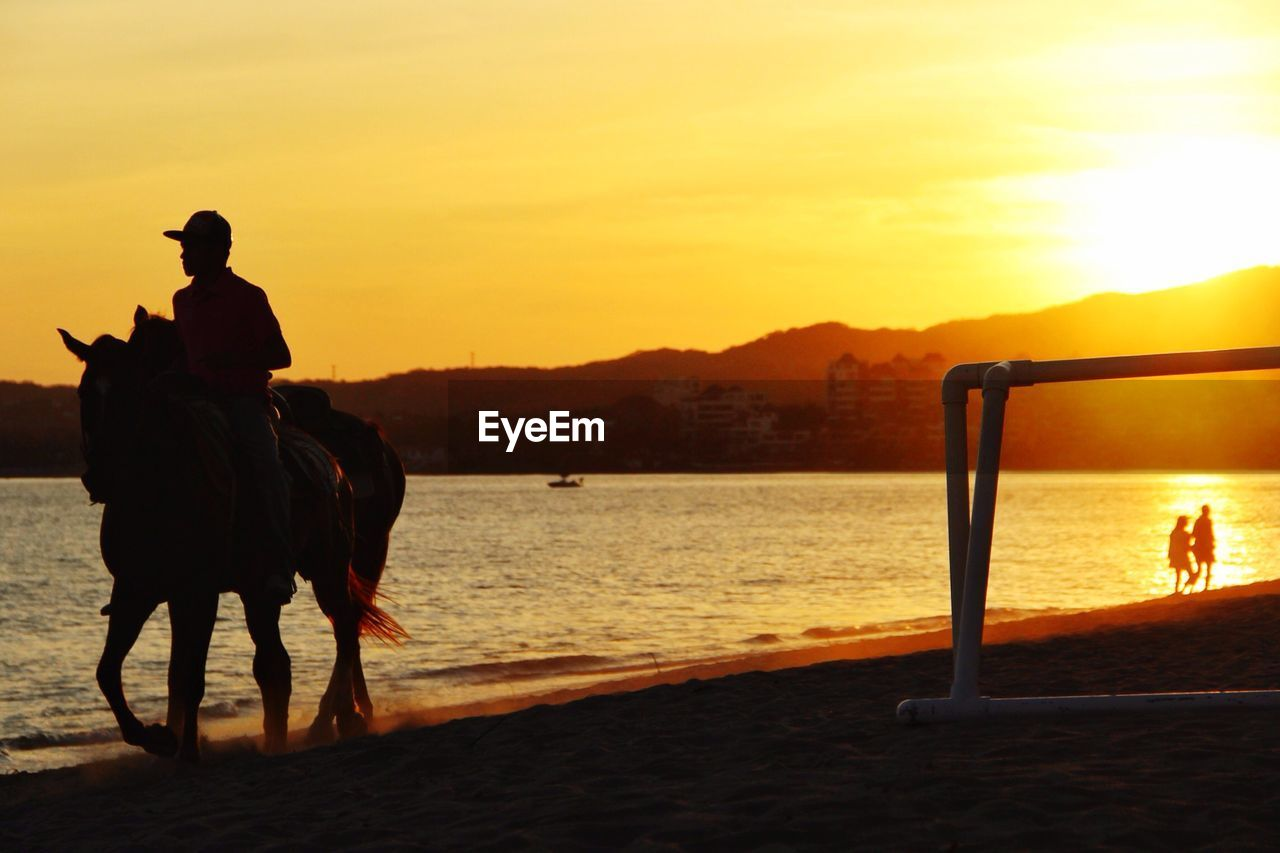 Person riding horse on beach at sunset
