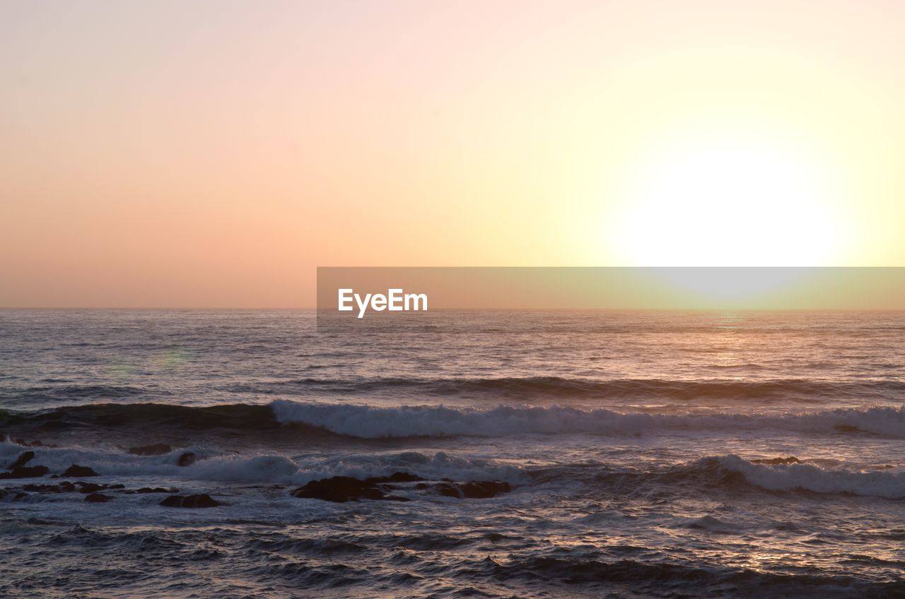 sea, sunset, sky, water, horizon over water, horizon, scenics - nature, beauty in nature, land, wave, motion, beach, orange color, tranquility, sun, nature, idyllic, tranquil scene, clear sky, no people, outdoors, power in nature, flowing water